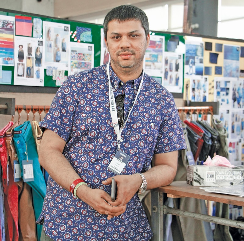 "As the global supply chain in garments gets more competitive, it is not only the vendors who are facing the heat. Buying agencies too are working out new strategies to service their clients and ensure that business remains with them. Synergies Sourcing Bangladesh Ltd. – the local sourcing arm of Synergies Worldwide with global headquarters in Bangkok, realizing that the country is not strong enough in product development, and which often can be a differentiator as all manufacturing bases make effort to reduce price, is now working on a full package model. ""We are not just into sourcing but operate as what we call a 'virtual' manufacturing company. We design our own collections and sell it to our customers as if we are the manufacturers,"" shares Atif Ahmed, Director of Synergies Sourcing Bangladesh Limited. The company maintains a development cell and design studio supervised by few internationally sourced expats to guide the predominantly local talents… ""And it has worked out pretty well for us,"" says Atif. The global supply chain managing company, which provides low-cost sourcing solutions in apparel, fashion accessories, footwear, home textiles, decorative accessories and other goods for retailers/brands in the fashion and hospitality industries, is sourcing different products from different manufacturing centers based on their core strength. In February this year Synergies Worldwide appointed former Li & Fung executive Guido Schlossmann as its new President and CEO, as founder Munir Mashooqullah of Pakistan retired after 28 years. Schlossmann takes over the reins of Synergies as the company hailed 2015 as its 'best year'. Adding its might to the company, Bangladesh operations today account for 50 per cent of total sourcing. ""The Bangladesh operation is worth around US $ 150 million; 60 per cent of business is in T-shirts, 25 per cent in denims and 15 per cent we do sweaters,"" underlines Atif, adding that in denims they cater mainly to Inditex Group, Mango, French retailers, Italian retailers, Brazilian retailers, German discounters and US-based apparel importers. Though the company is working hard to increase denim sourcing from Bangladesh, of late Atif is witnessing change in the global denim landscape, fueled primarily by increasing number of players in the market, due to which there is an oversupply in the market affecting margins of manufacturers and ticket prices of retailers. This has impacted global markets, emerging trends and the overall denim business. ""When the retailers are struggling to attract customers in a crowded marketplace, we too are not spared… If the front end comes in for fire, back end too has to bear the brunt. The risk increases even more when we do bigger programs and they don't sell, this means the retailers lose confidence in our ability to provide the right product/price and the liability builds up on our shoulders to be more competitive. The impact is higher in a country like Bangladesh which has certain financial constraints and is already working on thin margins,"" elucidates the Director of Bangladesh arm of Synergies worldwide. Atif shares that the global denim market is now moving towards cleaner looks in contrast to last year's ripped, teared and rugged approach, though different markets are reacting differently to this change with one aspect remaining constant for end-users as well as the retailers worldwide, and which is 'affordability'. ""We are basically a very Europe-focused company but in the last couple of years US is increasingly becoming easier for us to penetrate as they too have started following the trends in Europe, but in cheaper raw material,"" underlines Atif. He continues that by and large Europe is still seeking fashion and high quality, though Germany is an exception to this pattern. ""In Germany there are different levels; some discounters offer the basic and the most fashionable in the cheapest price bracket, while there are brands who despite the hard times are very quality-conscious and don't want to compromise on it…, they want to be in the league of their own. The European trendy look in denim is going to continue because, though there is price reduction, there is also simultaneously a marked improvement in 'looks' though quality-wise offerings may not always be the best,"" underlines Atif, who also doesn't foresee a major shift in manufacturing and sourcing pattern with respect to Asia, where the size of the Chinese business will remain despite its increasing wages and whatever shuffling happens will be in the basics and it will keep rotating within the region."
